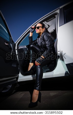Young woman in leather clotes with car