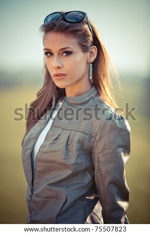 young woman in leather jacket and sunglasses outdoor portrait at sunset - stock photo