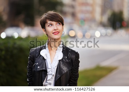 Young woman in leather jacket on a city street - stock photo