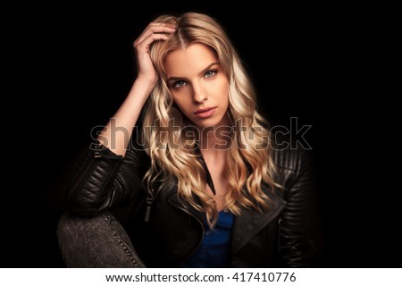 young woman in leather jacket resting her head on her palm and looks at the camera - stock photo