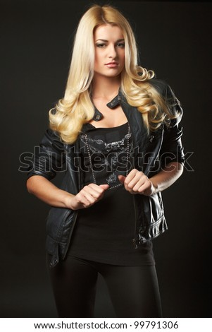 young woman in leather jacket, stdio shot, black background - stock photo