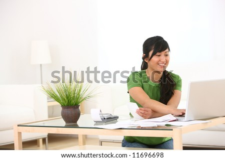 Young woman in living room with paperwork