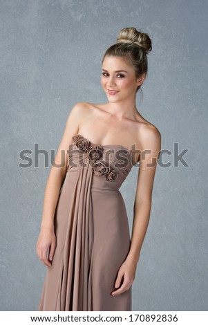 Young woman in long dress and hair in top knot bun on grey grunge studio background - stock photo