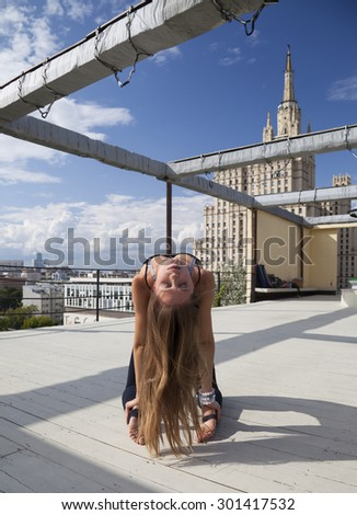 young woman in long dress on wooden roof in sunny day - stock photo