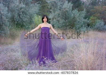 Young woman in long lilac dress. Very soft focus.