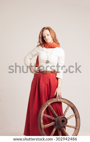 Young woman in long red skirt standing near the wheel of the cart - stock photo