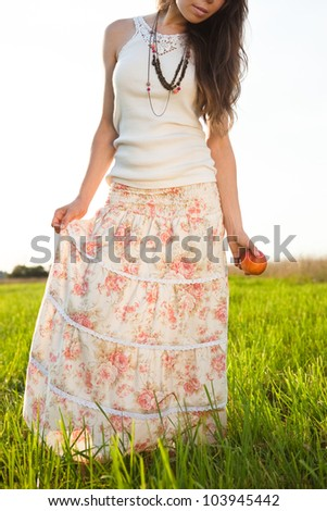 young woman in long skirt and tank top - stock photo