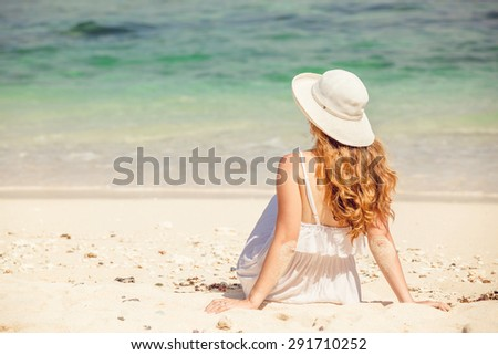 Young woman in long white dress and hat lying on white sand of tropical beach having great summer time on holidays. Summer vacation, holidays, serenity, travel, lifestyle concept  - stock photo