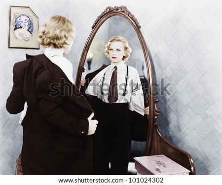 Young woman in men's clothing getting undressed in front of a mirror - stock photo