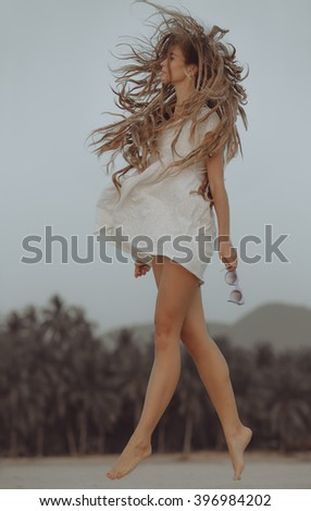 Young woman in milky dress jumping in the sunset on the beach