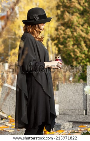Young woman in mourning adorating husband's grave - stock photo