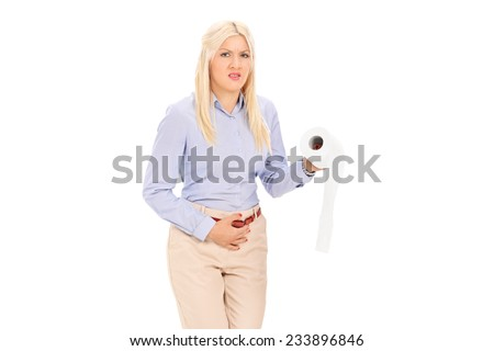 Young woman in need to pee holding a toilet paper isolated on white background - stock photo