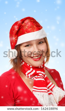 Young woman in new year or christmas suit smiling on blue background with falling snow