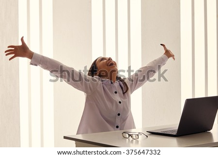Young woman in office jubilation at desk.