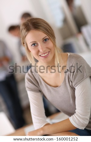 Young woman in office, people in background