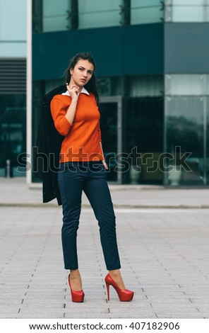 Young woman in orange jersey. Outdoor photo in the city. - stock photo