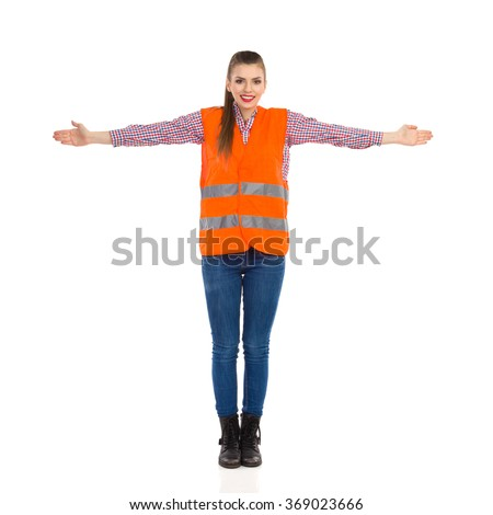 Young woman in orange reflective vest, lumberjack shirt, jeans, black boots,standing with horizontally arms outstretched. Full length studio shot isolated on white. - stock photo