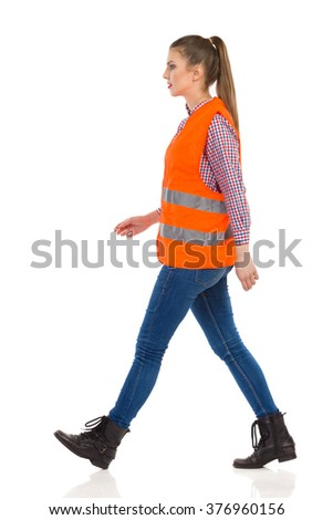 Young woman in orange reflective vest, lumberjack shirt, jeans, black boots, walking and looking away. Side view. Full length studio shot isolated on white.