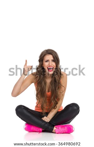 Young woman in orange shirt, black leather trousers and pink sneakers sitting on a floor with legs crossed, pointing up and shouting. Full length studio shot isolated on white.