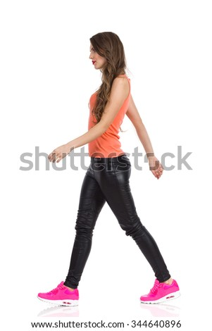 Young woman in orange shirt, black leather trousers, pink sneakers walking and looking away. Full length studio shot isolated on white. - stock photo