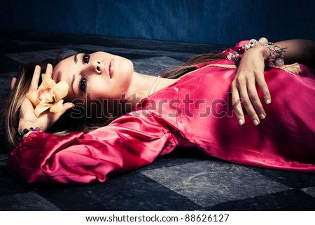 young woman in oriental dress holding flower orchid in hand, indoor shot - stock photo