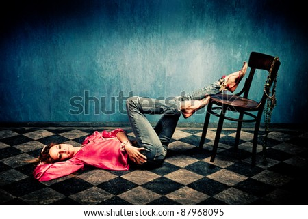 young woman in oriental shirt and shoes lie on tiled floor, legs on chair, studio shot - stock photo