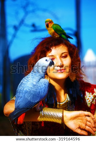Young woman in ornamental dress and beautiful gold jewelry with a color parrots.