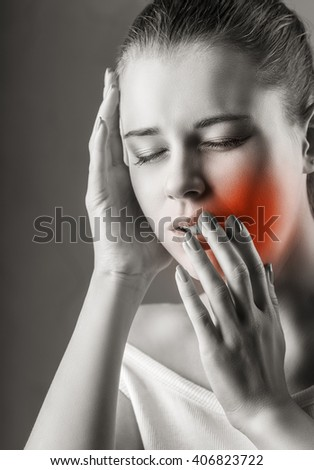 Young woman in pain is having a toothache - stock photo