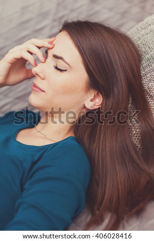 Young woman in pain, lying down on the couch in the living room - stock photo