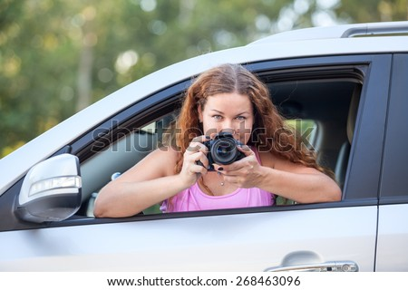 Young woman in pink t-shirt with a camera in hand taking pictures of the car - stock photo