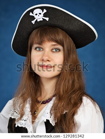 Young woman in pirate hat on blue background - stock photo