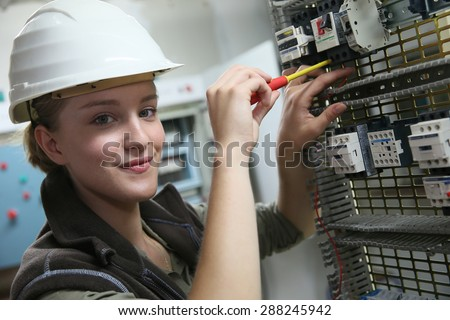 Young woman in professional training setting up electrical circuit - stock photo