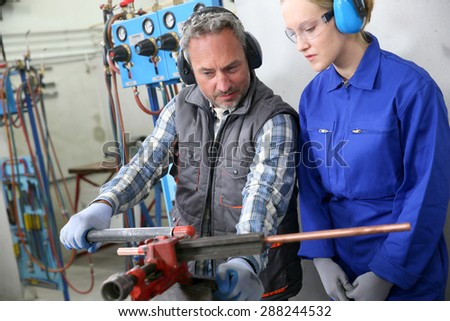 Young woman in professional training to become plumber - stock photo
