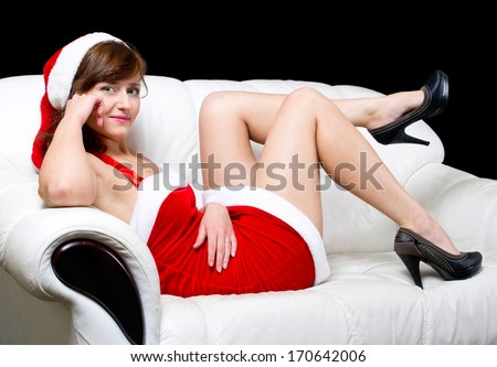 Young woman in red christmas dress lying on white sofa