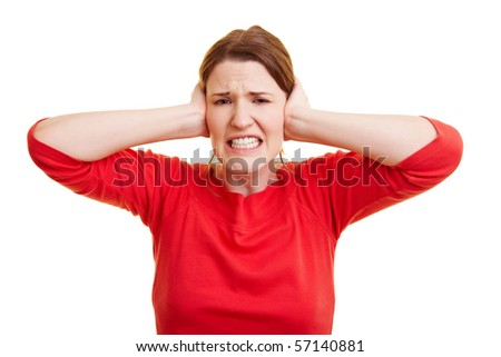 Young woman in red closing her ears - stock photo