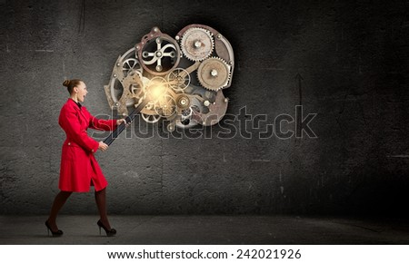 Young woman in red coat fixing mechanism with wrench - stock photo