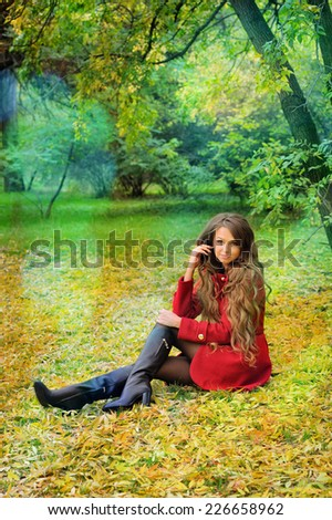 Young woman in red coat sitting in autumn park.