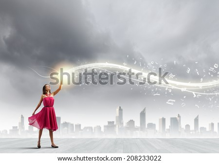 Young woman in red dress against city background - stock photo