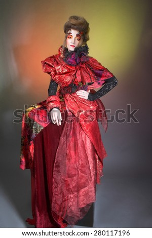 Young woman in red dress and with artistic visage and hairstyle. - stock photo