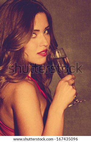 young woman in red dress hold a glass of champagne  retro colors - stock photo