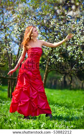 Young woman in red dress in cherry garden. - stock photo