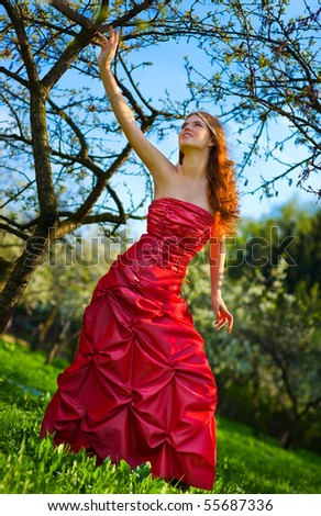 Young woman in red dress in cherry garden. Camera angle view. - stock photo