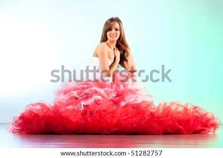 Young woman in red dress sitting on a floor. - stock photo