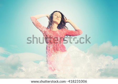 Young woman in red dress standing in the clouds The image with the effect of double exposure