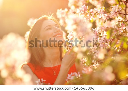 Young woman in red dress walking in garden - stock photo