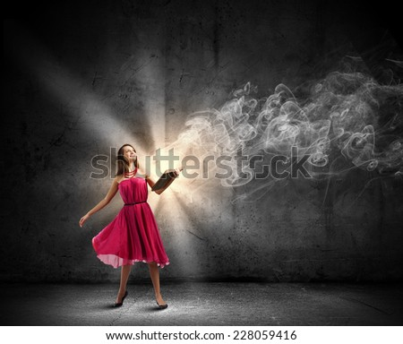 Young woman in red dress with book in hand - stock photo
