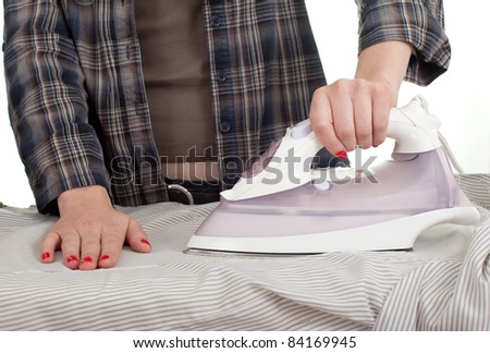 young woman in red headscarf ironing clothes, housework - stock photo