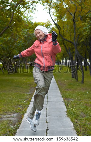 Young woman in red jacket jumps and have a fun in the park - stock photo