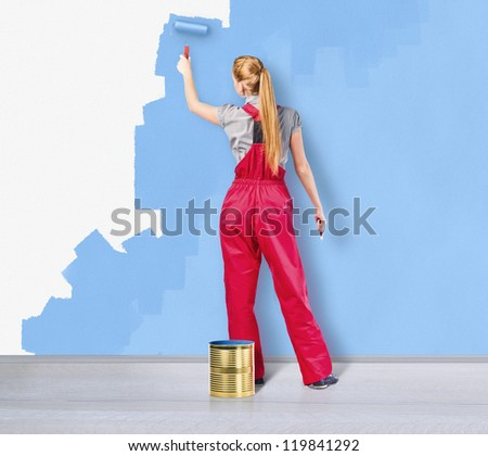 Young woman in red overalls with painting tools - stock photo