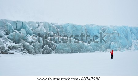 Young woman in red standing in front the blue glacier in cold snowy winter day, Greenland - stock photo